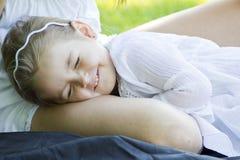 A little girl sleeps with her mom Stock Image