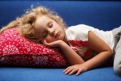Little girl sleeps on a sofa Stock Photos