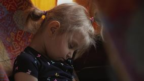The little girl sleeps soundly on the seat of the bus during the journey. Little cute girl sleeping soundly on the seat of the bus during the trip stock video
