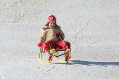 Little girl on a sleigh Stock Photos