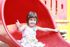 Little girl on the slide Stock Photos