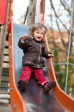 Little girl at the slide. Little girl is sliding at the playground Royalty Free Stock Image