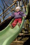 Little girl on slide Stock Images