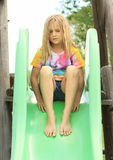 Little girl on a slide. Barefoot girl in colorful t-shirt sitting on green slide stock image