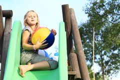 Little girl on a slide with inflating ball Royalty Free Stock Photo
