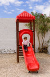 The little girl on the slide at the site. Stock Photos