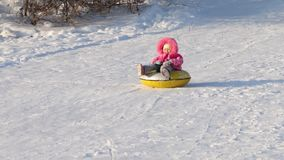 Little girl slides on snowtube down from hill at sunny winter day stock video footage