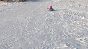 Little girl slides on snowtube from hill, two unrecognizable adults and child are on hill. N stock video footage