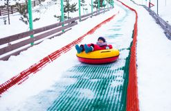 Little girl sliding down the hill by tubing royalty free stock photography