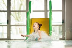 Little girl sliding down the water slide Royalty Free Stock Photos