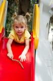 Little girl sliding from the plastic chute stock photos
