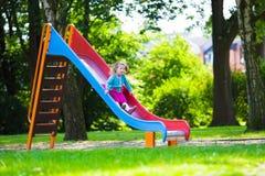 Little girl sliding on a playground Stock Image