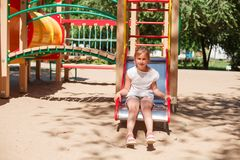 Little girl is sliding at playground. Cute blonde little girl is sliding at playground. She is sitting on the slide. Horizontal image Stock Image
