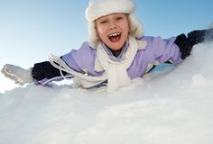 Little girl sliding in the snow Stock Photos