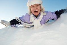 Little girl sliding in the snow Stock Photos