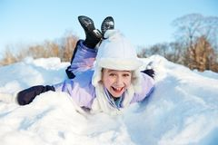 Little girl sliding in the snow Stock Photo