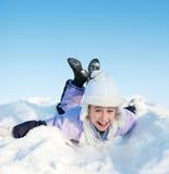 Little girl sliding in the snow Stock Images