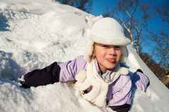Little girl sliding in the snow Stock Images