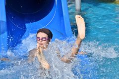 Little girl sliding in the water slide during vacation in sommer. Flowing water Royalty Free Stock Photography