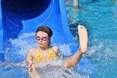 Little girl sliding in the water slide during vacation in sommer. Flowing water Stock Photos