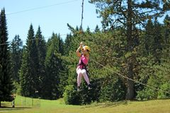 Little girl sliding on a zip line extreme park Royalty Free Stock Photo