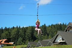 Little girl sliding on a zip line Stock Photos
