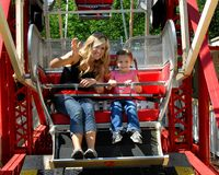 Apprehensive About First Ferris Wheel Ride. Little girl is slightly apprehensive about her first Ferris Wheel Ride. Her Mom, sitting besides her, tries to cheer stock image
