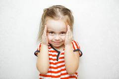 Little girl with sly smile slightly covers her face royalty free stock images