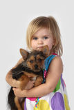 Little girl with small dog on gray Royalty Free Stock Photography