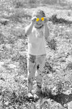 Little girl with 2 flowers. Small girl in the meadow with 2 yellow flowers Royalty Free Stock Image