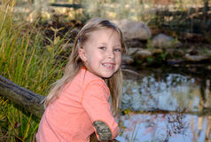 Little girl by a small pond in the garden Royalty Free Stock Photography