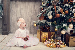 Little girl in a smart dress sits near a Christmas tree Stock Photo