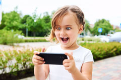 Little girl with a smartphone Stock Images