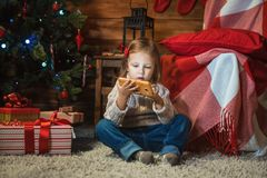 Girl with smartphone at home with a Christmas tree, presents and. Little girl with smartphone at home with a Christmas tree, presents and candles celebrating Royalty Free Stock Image