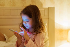 Little girl with smartphone lying in a bed, bedtime Stock Photo