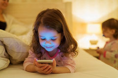 Little girl with smartphone lying in a bed, bedtime Stock Image