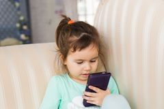 Little girl with smartphone in room stock photos
