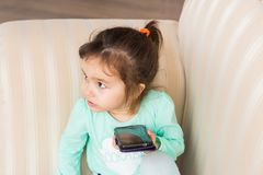 Little girl with smartphone in room stock images