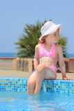 Little girl smeared with cream for sunburn on pool Stock Image
