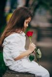 Little girl smell rose outdoor. Little and pretty girl smell rose outdoor in white suit Stock Photography