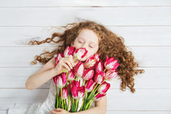 Little Girl smell of tulips and closed her eyes. Royalty Free Stock Images