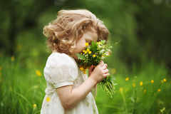 Little girl smelling a bouquet of flowers Royalty Free Stock Photo