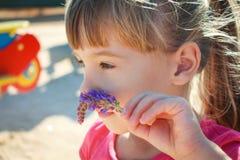 Little girl smelling a flower Stock Image