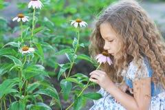 Little girl smelling flower garden Royalty Free Stock Photography