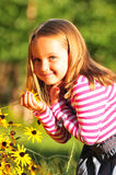 Little girl smelling a flower royalty free stock images