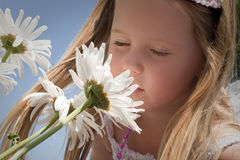 Little girl smelling flowers royalty free stock photos