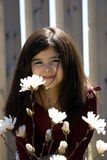 Little girl smelling the flowers. A little girl leaning in and smelling a flower, while smiling at the camera Stock Images