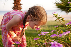 Little girl smelling flowers on the beach. Royalty Free Stock Photography