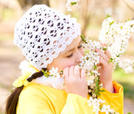Little girl smelling flowers outdoors Royalty Free Stock Photos