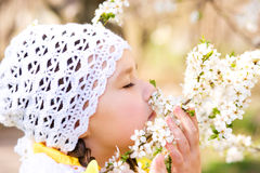 Little girl smelling flowers outdoors Stock Image